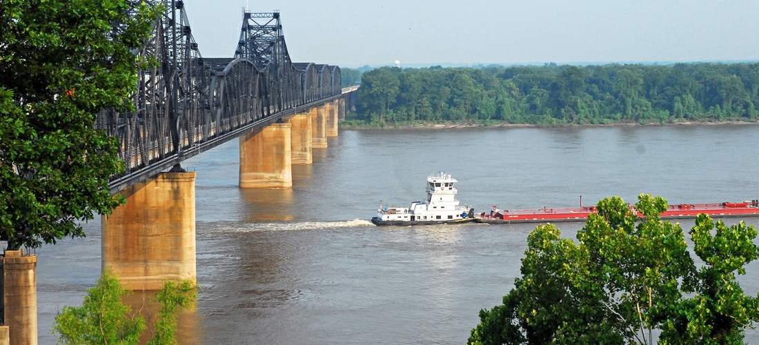Vicksburg bridge over the Mississippi River with a passing barge.